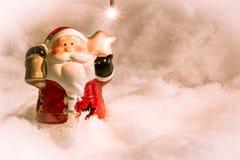 圣诞老人举行响铃和星在雪站立 免版税库存图片