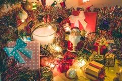 圣诞老人举行响铃和白色和紫罗兰色蜡烛、装饰品和圣诞节装饰圣诞快乐夜和新年好 库存图片