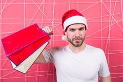 圣诞老人人推力重量纸袋在强的手上 免版税库存照片