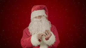 圣诞老人从他的在红色背景的手机读并且发正文消息与雪 免版税图库摄影