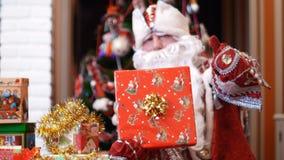 圣诞老人克劳斯,父亲圣诞节,父亲弗罗斯特在他的手上举行,在手套在一张红色包装纸的一件大圣诞节礼物 股票视频
