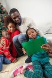 读给圣诞老人写的信的女孩 免版税库存图片