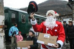 圣诞老人分享甜点给游人 免版税库存图片