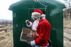 圣诞老人分享甜点给游人 免版税库存照片
