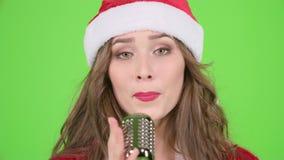圣诞老人助理衣服的女孩在一个减速火箭的话筒唱歌并且跳舞与精力充沛的音乐 绿色屏幕 慢 股票视频