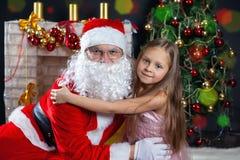 圣诞老人和一个女孩礼服的 圣诞节场面 库存照片