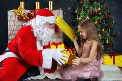 圣诞老人和一个女孩礼服的 圣诞节场面 免版税库存照片