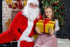 圣诞老人和一个女孩礼服的 圣诞节场面 图库摄影