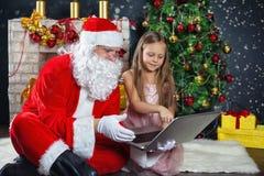 圣诞老人和一个女孩礼服的 圣诞节场面 免版税库存图片