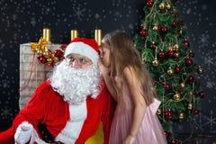 圣诞老人和一个女孩礼服的 圣诞节场面 库存图片