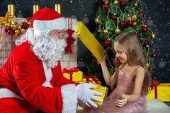 圣诞老人和一个女孩礼服的 圣诞节场面 免版税图库摄影