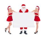 圣诞老人和两名愉快的逗人喜爱的雪少女妇女有圣诞节的 库存图片