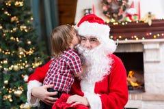 圣诞老人和儿童男孩 告诉的孩子他的 库存照片