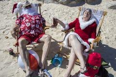 圣诞老人和克劳斯夫人分享在海滩的一个热带鸡尾酒 免版税库存图片
