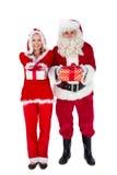 圣诞老人和克劳斯夫人微笑对照相机提供的礼物的 免版税图库摄影