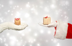 圣诞老人和冬天手套递拿着礼物盒 库存照片