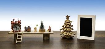 圣诞老人和天使与圣诞树、红色时钟和空白的黑照片框架 免版税库存照片