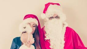 圣诞老人和妇女有christmassy帽子的 免版税库存照片