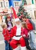 圣诞老人和孩子在庭院里 免版税库存照片