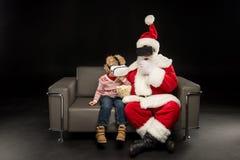 圣诞老人和孩子有虚拟现实耳机的 免版税库存图片