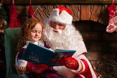 圣诞老人和小女孩阅读书 免版税库存照片