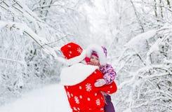 圣诞老人和有女婴的在冬天森林里 免版税库存照片
