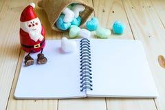 圣诞老人和空白的笔记本和蓝色白色心脏从大袋 图库摄影
