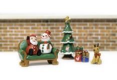圣诞老人和雪人坐绿色长凳在驯鹿和礼物附近 免版税库存图片