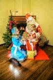 圣诞老人和雪未婚提出了一件礼物给女孩 年龄5 免版税库存照片