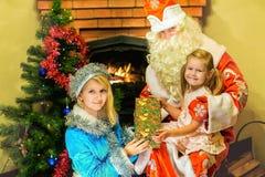 圣诞老人和雪未婚提出了一件礼物给女孩 年龄5 图库摄影