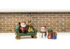 圣诞老人和驯鹿坐绿色长凳在雪人附近并且presen 免版税库存图片