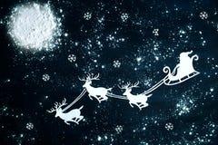 圣诞老人和驯鹿飞行通过夜空 库存图片