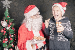 圣诞老人和滑稽的男孩用曲奇饼和牛奶在圣诞节 免版税库存照片