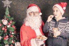 圣诞老人和滑稽的男孩用曲奇饼和牛奶在圣诞节 免版税图库摄影