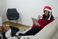 圣诞老人圣诞节在沙发的妇女读书 库存照片
