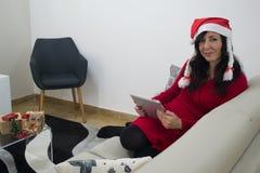 圣诞老人圣诞节在沙发的妇女读书 免版税图库摄影