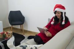 圣诞老人圣诞节在沙发的妇女读书 库存图片