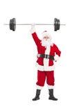 圣诞老人在一只手上的拿着重的杠铃 免版税图库摄影