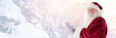 圣诞老人在与片剂的冬天 免版税库存图片