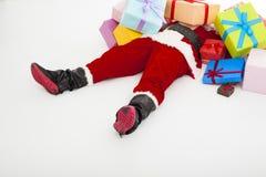 圣诞老人在与许多礼物盒的地板上也疲倦说谎 免版税图库摄影