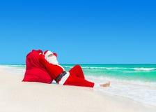圣诞老人在圣诞节礼物大袋晒日光浴在海洋海滩 免版税图库摄影