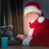 圣诞老人在打字机写一封信 免版税库存图片
