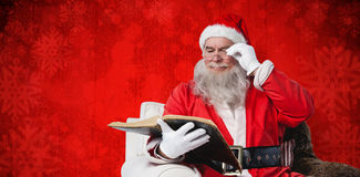 圣诞老人在扶手椅子的读书圣经的综合图象 免版税库存照片