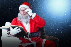 圣诞老人在扶手椅子的读书圣经的综合图象 库存照片