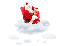 圣诞老人在拿着袋子和礼物的云彩安装了 库存图片