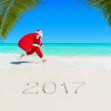 圣诞老人在有圣诞节大袋的棕榈滩跑2017年 库存照片