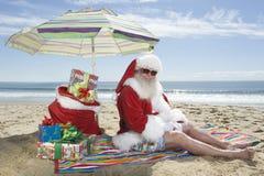 圣诞老人在有礼物的遮阳伞下坐海滩 库存图片