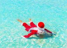 圣诞老人在海洋水中放松游泳,圣诞节旅行的c 免版税库存照片