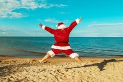 圣诞老人在海滩跳 免版税库存图片