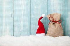 圣诞老人在雪的帽子和礼物袋子 图库摄影